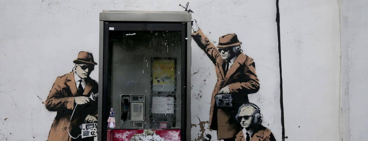 CHELTENHAM, ENGLAND - APRIL 14: A piece of new graffiti street art, claimed to be by the secretive underground guerilla artist Banksy, which appeared on the side of a house in Cheltenham this weekend, is seen on April 14, 2014 in Gloucestershire, England. The artwork, which shows three stencil figures listening into a conversation in an existing telephone box, is just a few miles away from Government Communications Headquaters (GCHQ), which is responsible for providing intelligence and information assurance to the British Government and Armed Forces. (Photo by Matt Cardy/Getty Images)