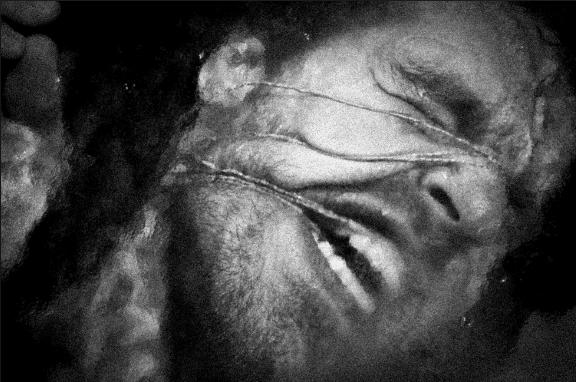 Fotografia live di Danny Willems (proiettata in scena in tempo reale) Il volto del danzatore legato e schiacciato sul vetro booty Looting regia di Wim Vandekeybus, Ultima Vez Teatro alle Tese, Venezia 2012 Per gentile concessione del fotografo