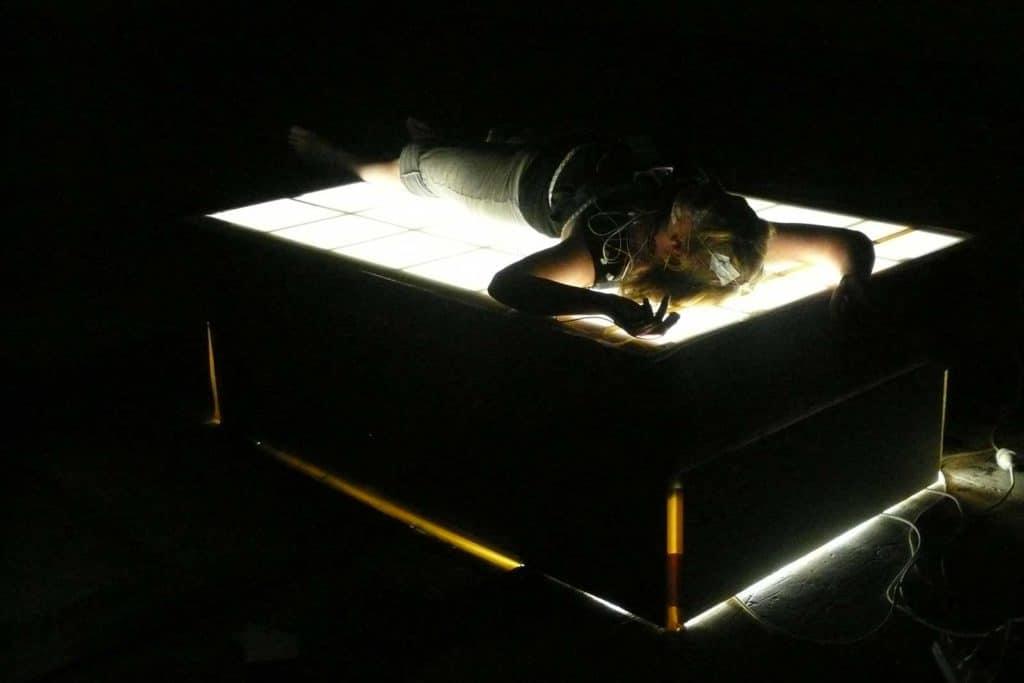 Riposo a turni. Una Light therapy box luminosa costruita come un letto per sperimentare le posizioni del sonno. <em>The Waking Incubator: scienza del sonno e arti dello spettacolo in dialogo</em>, Massey University NZ (2010). C. Brown, performer con EEG.