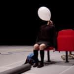 Kinkaleri. I Cenci/Spettacolo. 2004. Cristina Rizzo gonfia un palloncino senza mani, occhi al soffitto, seduta su una sedia rossa © Foto Monica Maggio.