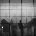 Città di Ebla. The dead. 2012. Foto in bianco e nero di donna che guarda mobili coperti da lenzuola. © foto di Gianluca