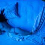 Città di Ebla.The dead. 2012. Foto virata in blu di donna che si muove nel letto. © foto di Luca di Filippo.