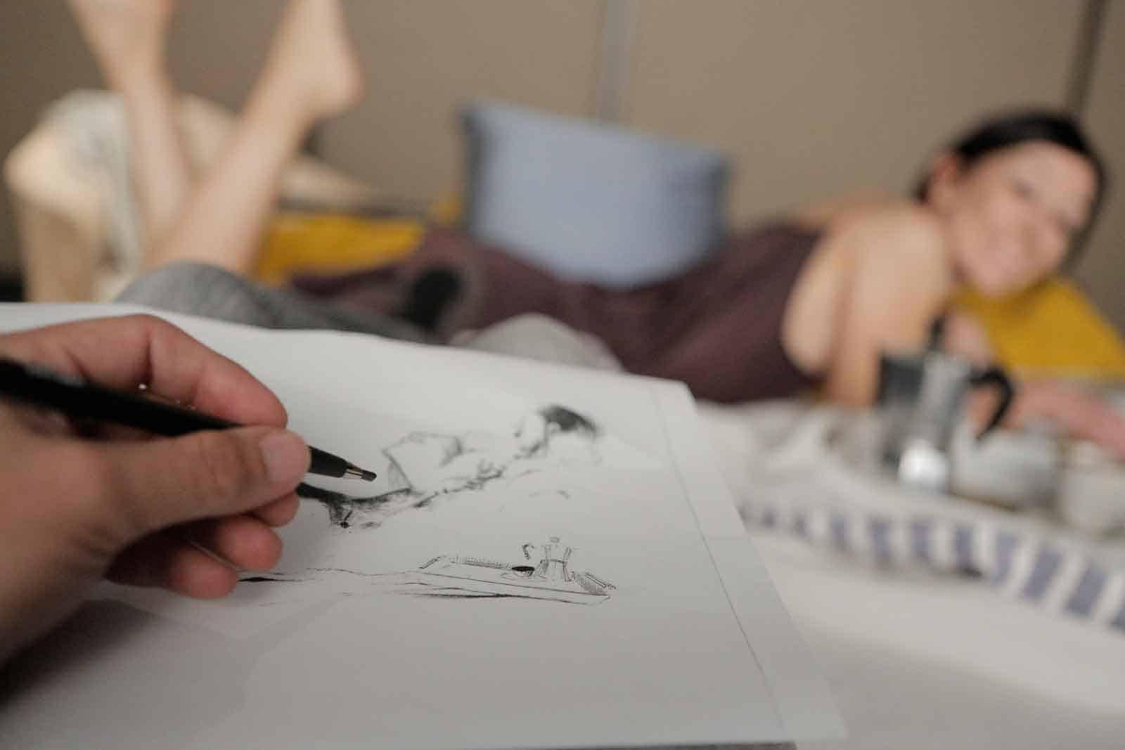Città di Ebla.The dead. 2012. Particolare di mano che esegue un ritratto e sullo sfondo Valentina Bravetti distesa. © foto di Luca di Filippo.