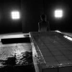 Città di Ebla. Pharmakos V. 2008. Donna in piedi con alle spalle il tavolo anatomico si avvia verso le luci. © foto di Gianluca