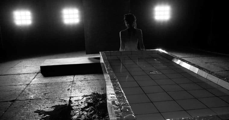 """Città di Ebla. Pharmakos V. 2008. Donna in piedi con alle spalle il tavolo anatomico si avvia verso le luci. © foto di Gianluca """"naphtalina"""" Camporesi."""